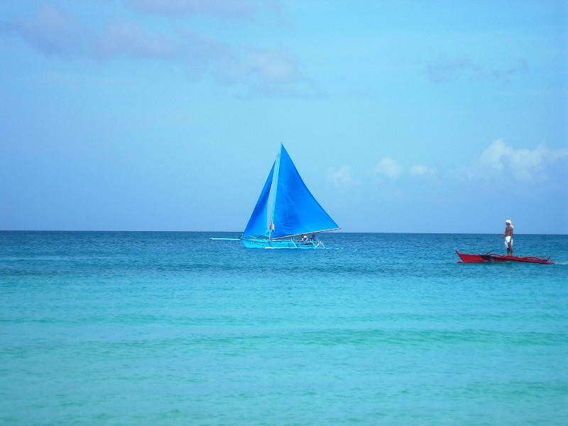 a lone sailboat proudly glides the calm waves of Boracay waters